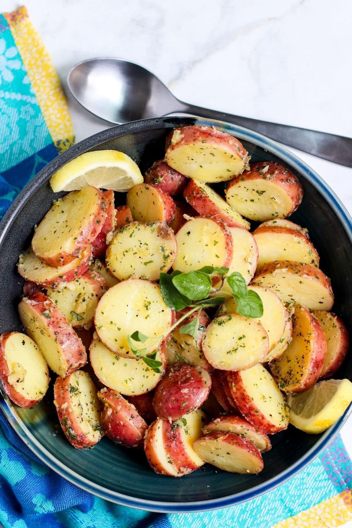 Bowl of Greek potato salad garnished with lemon slices and sprig of oregano