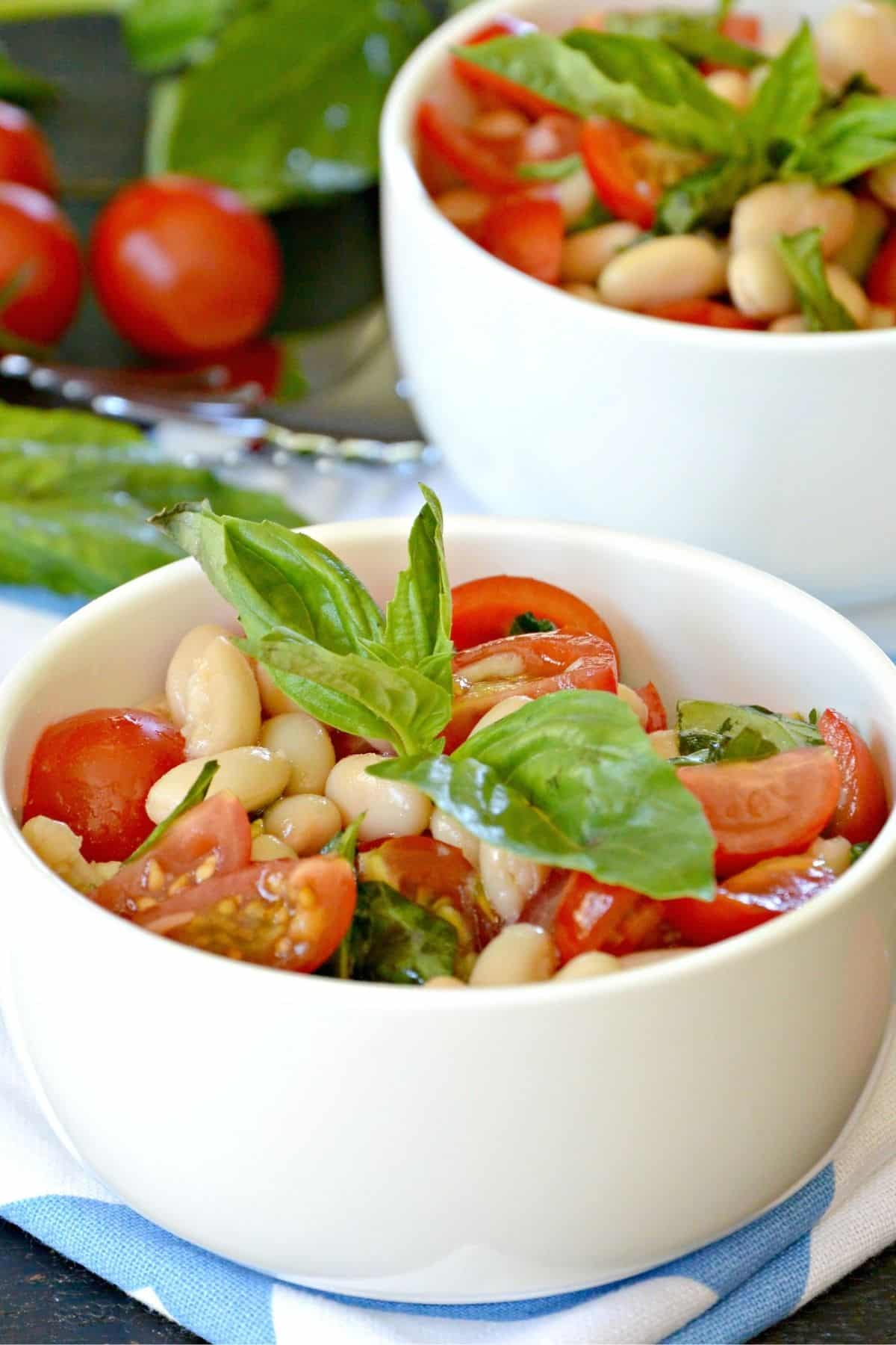 Bowls of Italian White Bean Salad topped with sprigs of fresh basil