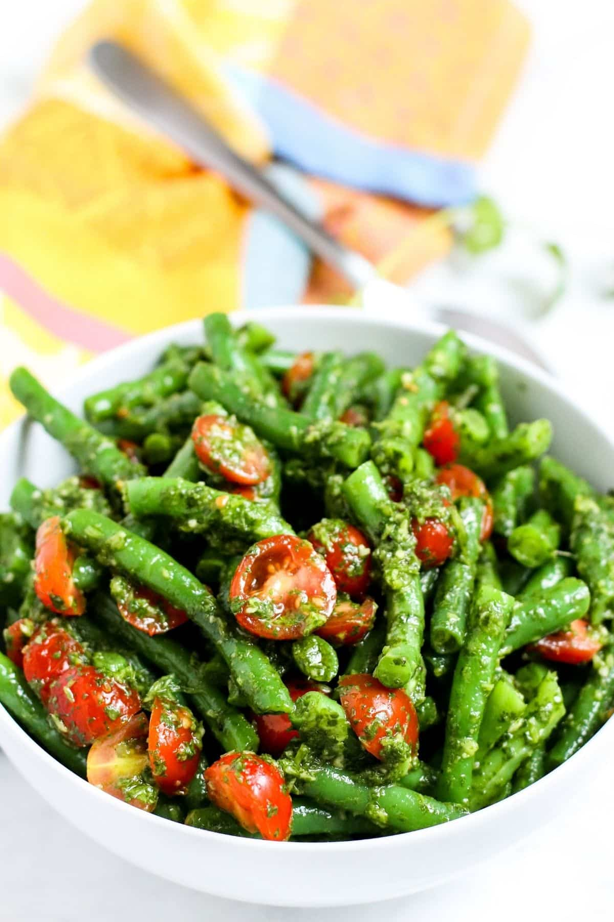 Bowl of green beans salad with cherry tomatoes topped with cilantro sauce
