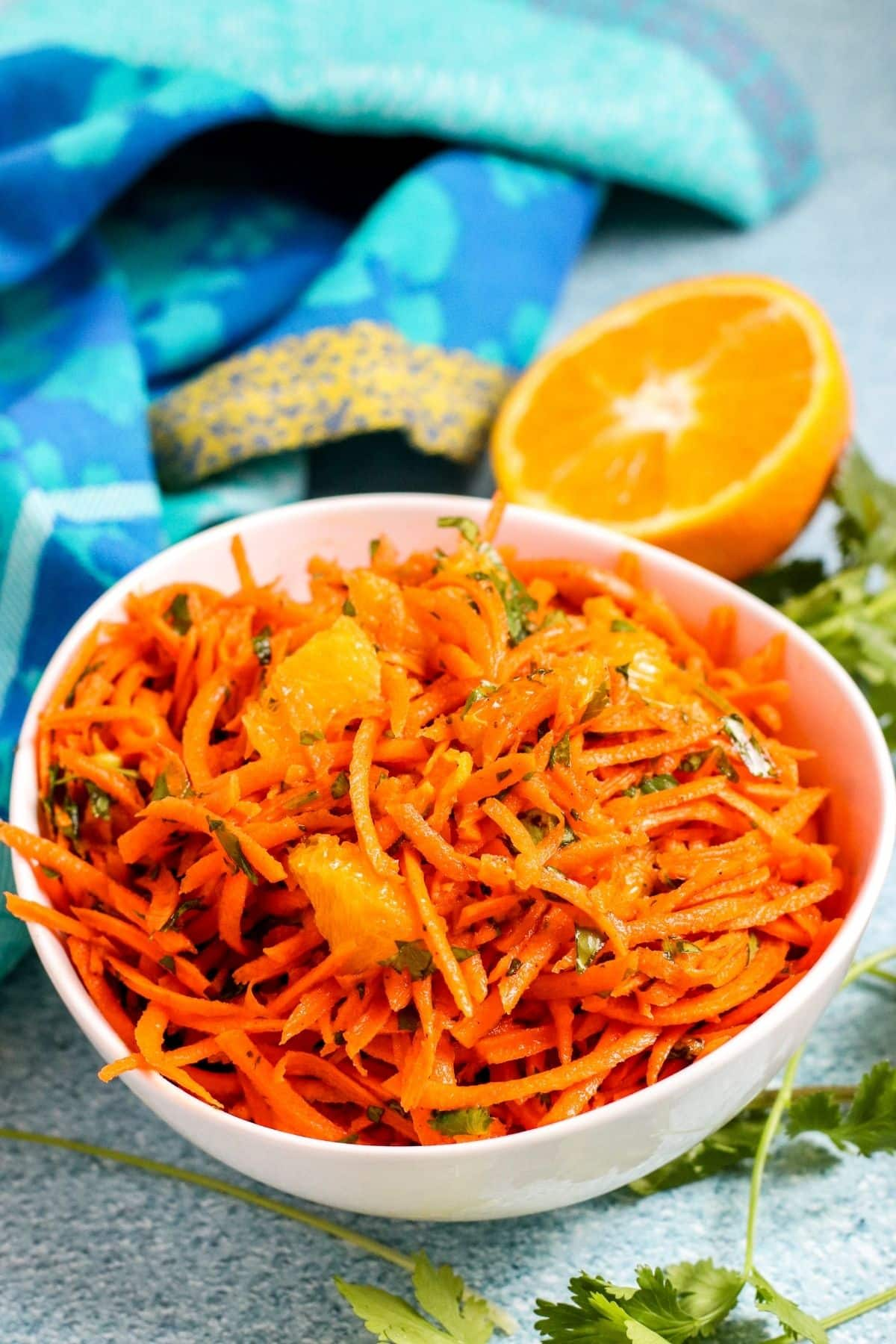 White bowl filled with shredded carrot salad with cut orange in the background