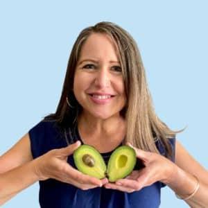 Amy holding a cut avocado like a heart