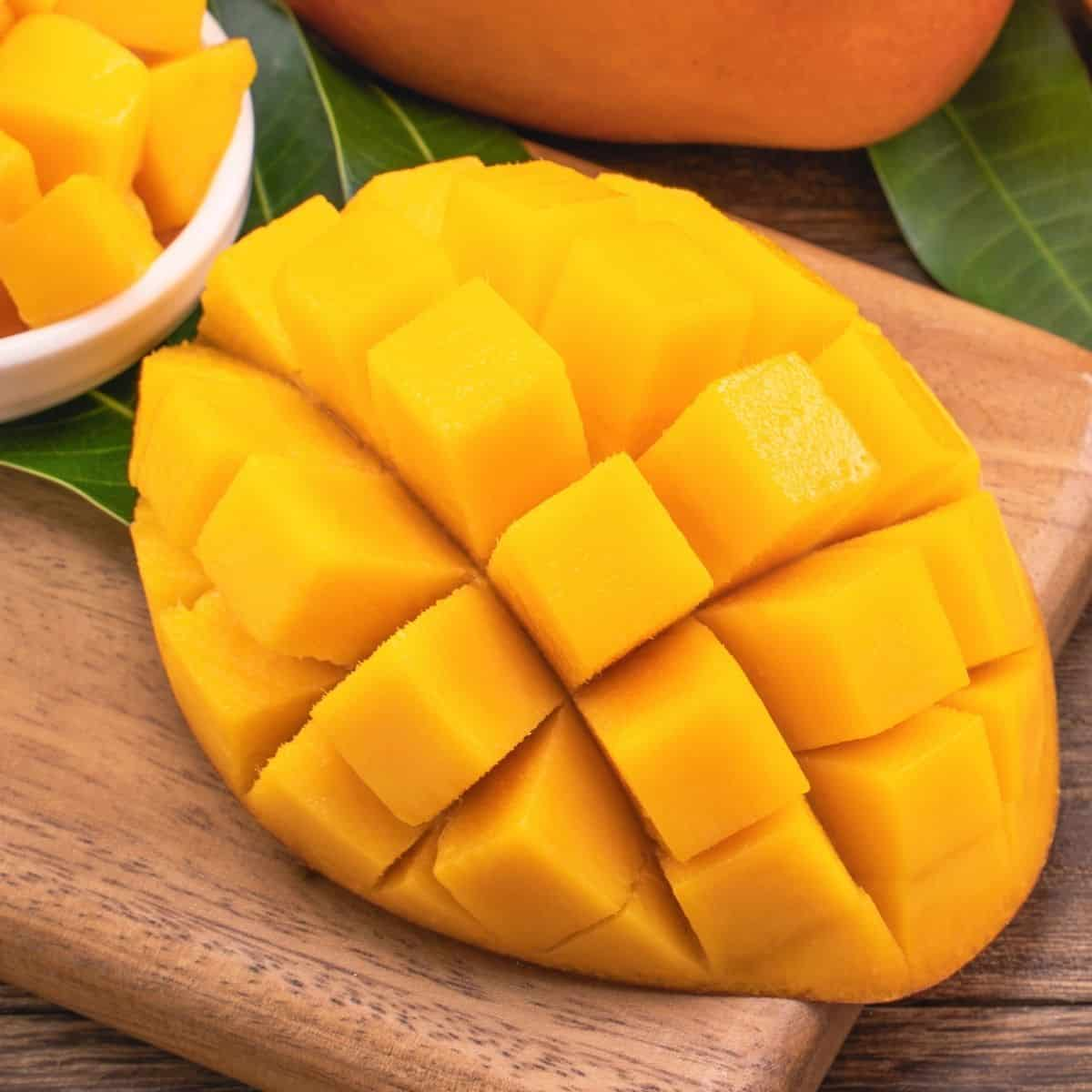 Mango on a cutting board sliced into a grid pattern to form cubes
