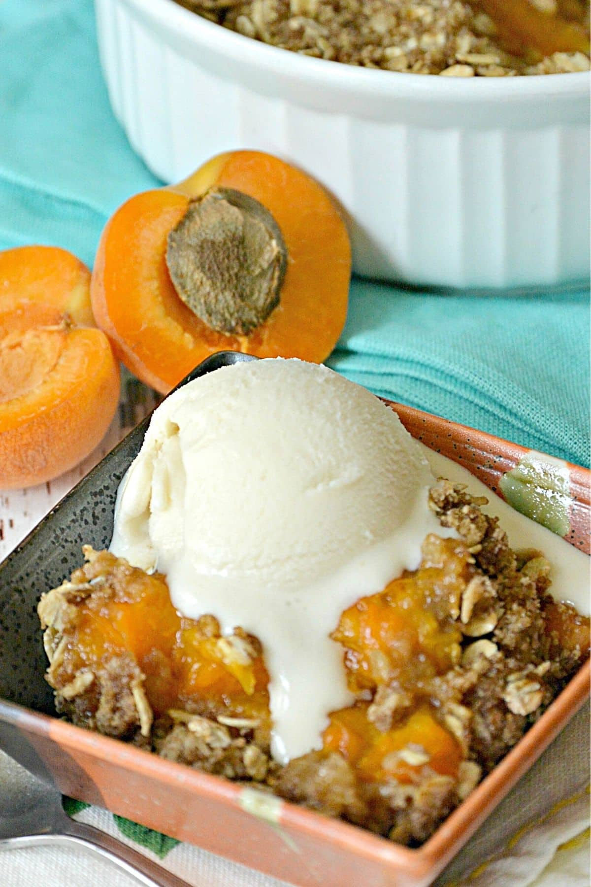 Serving of baked apricot dessert topped with scoop of vanilla ice cream