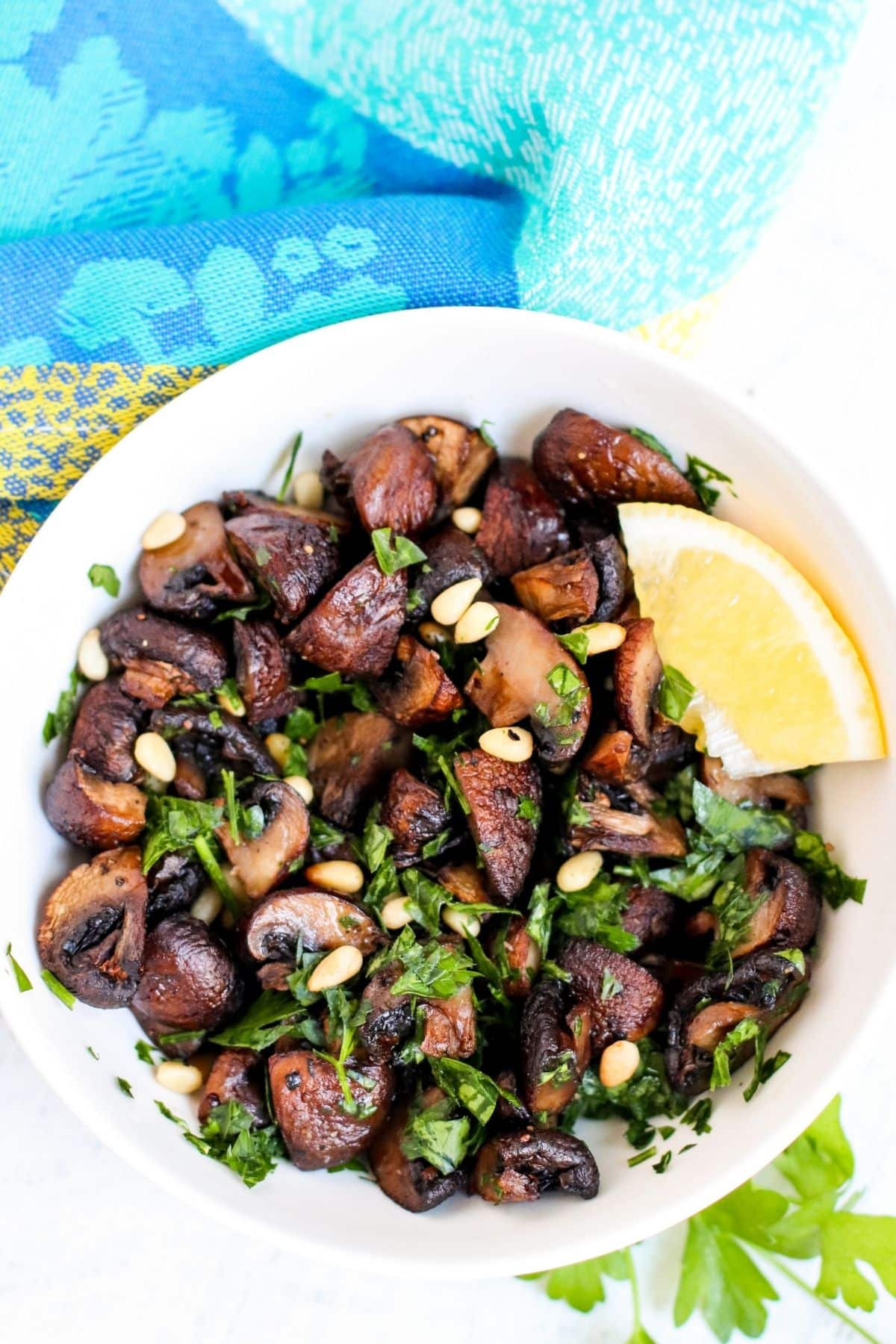 Bowl of roasted baby bella mushrooms topped with pine nuts and chopped parsley