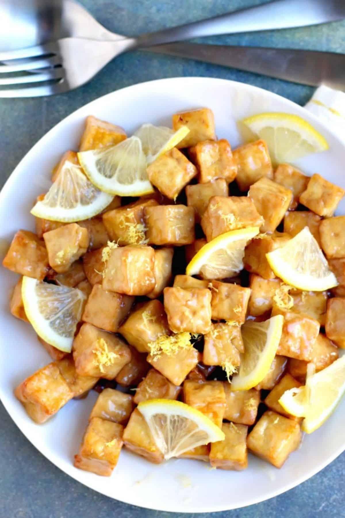 Platter of lemon tofu garnished with slices of fresh lemon