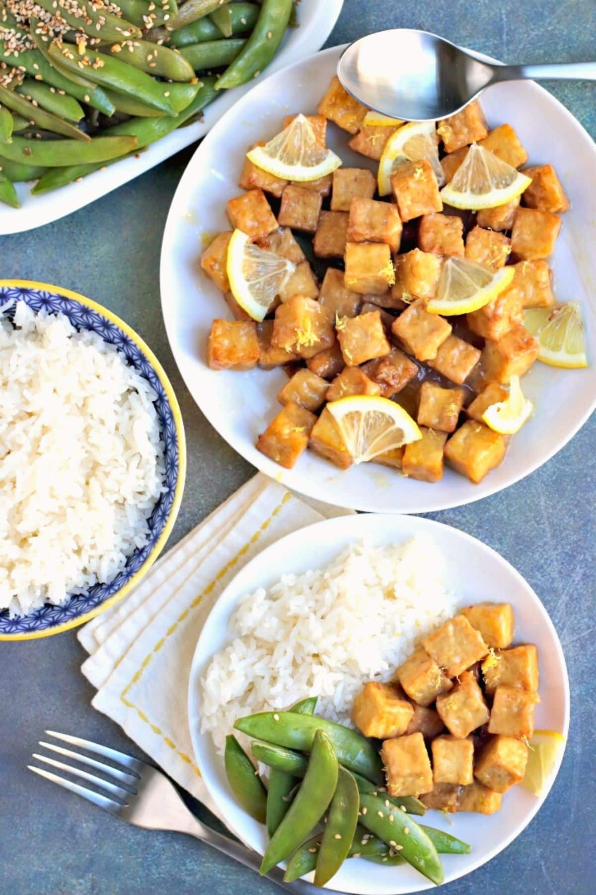 Platter of tofu with lemon sauce, bowl of rice, and dinner plate with rice, tofu, and sugar snap peas