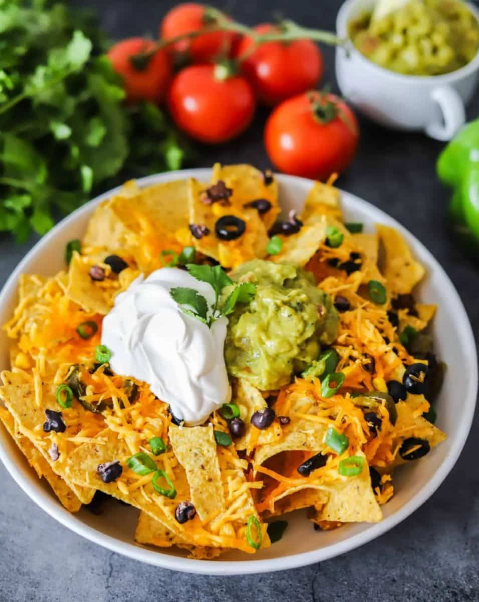 Platter of nachos topped with sour cream and guacamole