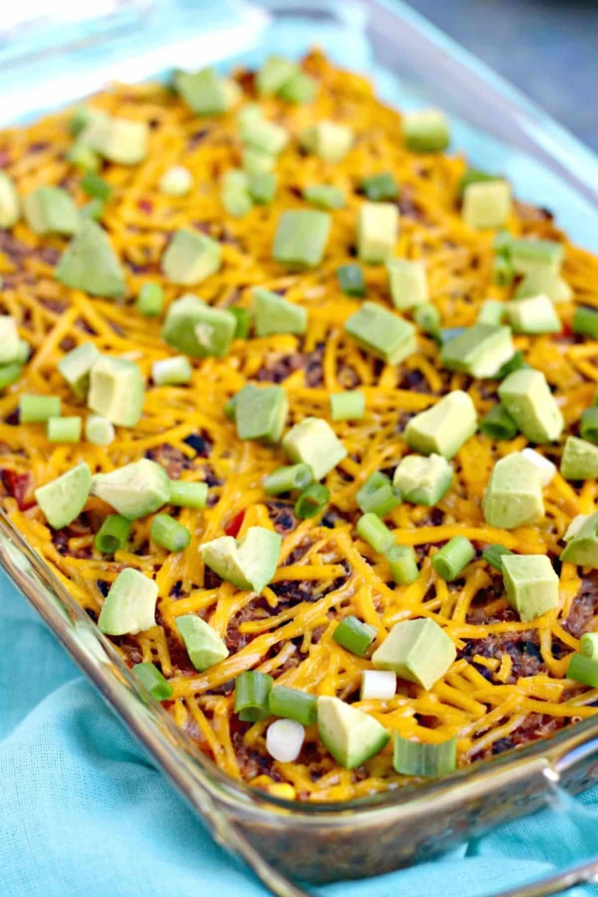 Baked casserole topped with sliced green onions and cubed avocado