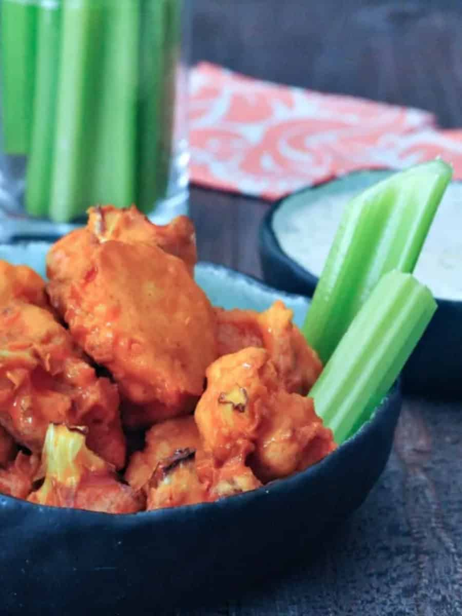 Buffalo cauliflower with celery sticks and bowl of Ranch dressing