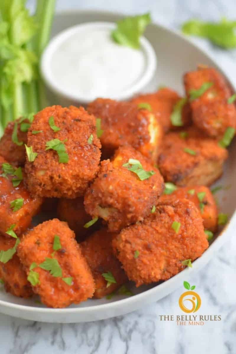 Buffalo tofu nuggets in a bowl with celery sticks and Ranch dressing