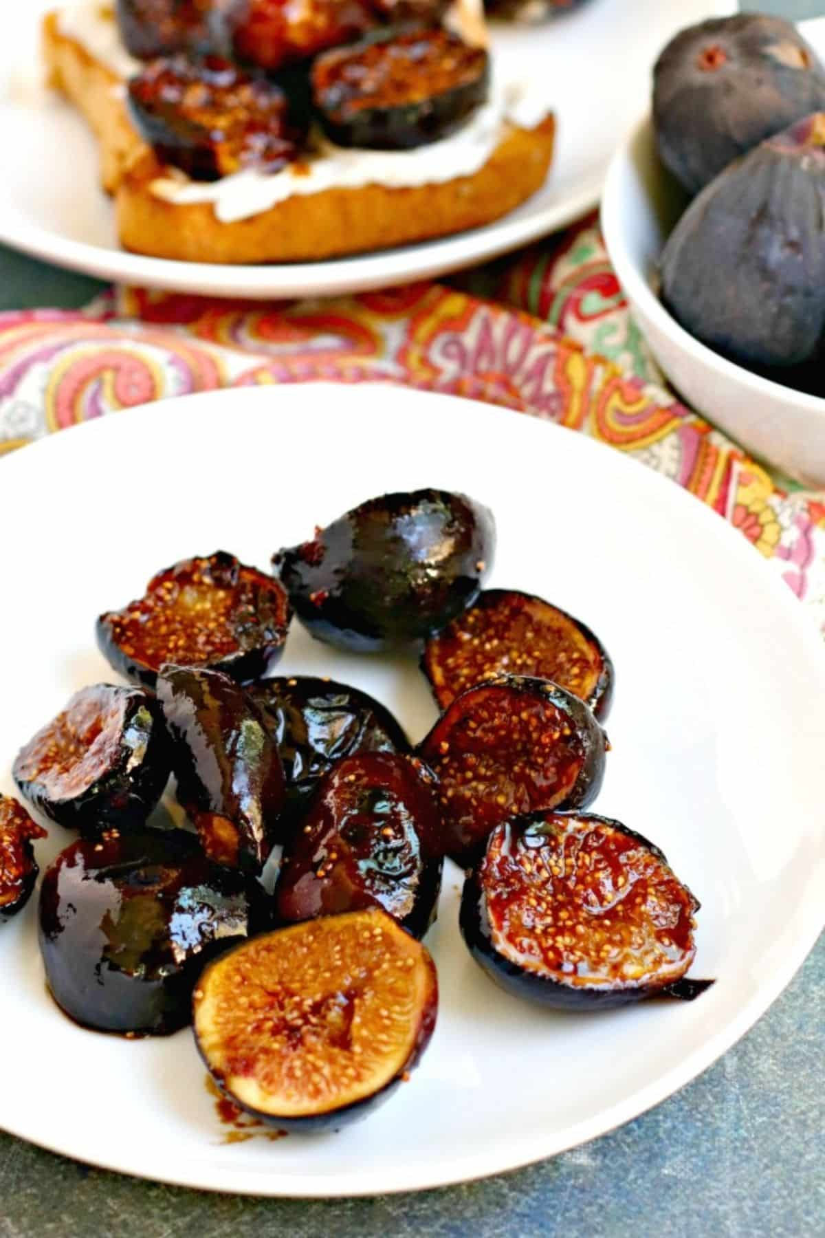 Caramelized figs on a plate with toast and bowl of fresh figs in the background