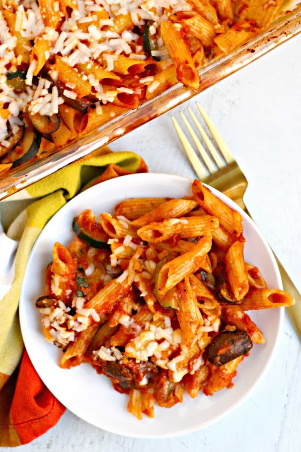 Plate of baked penne pasta with casserole in the background