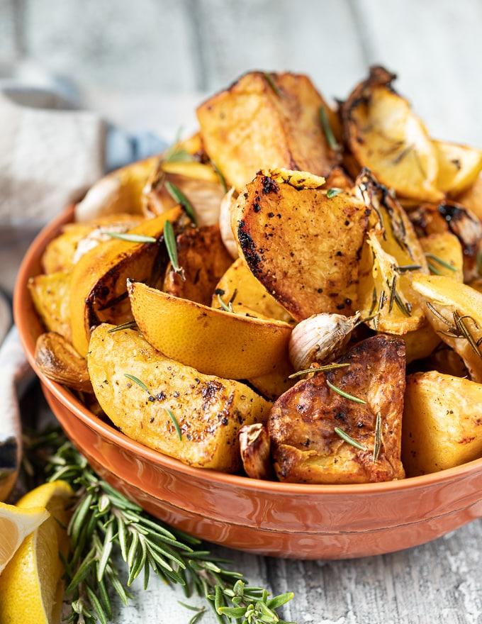 Bowl of roasted potatoes garnished with lemon