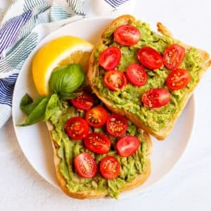 Plate with avocado toast and lemon wedge