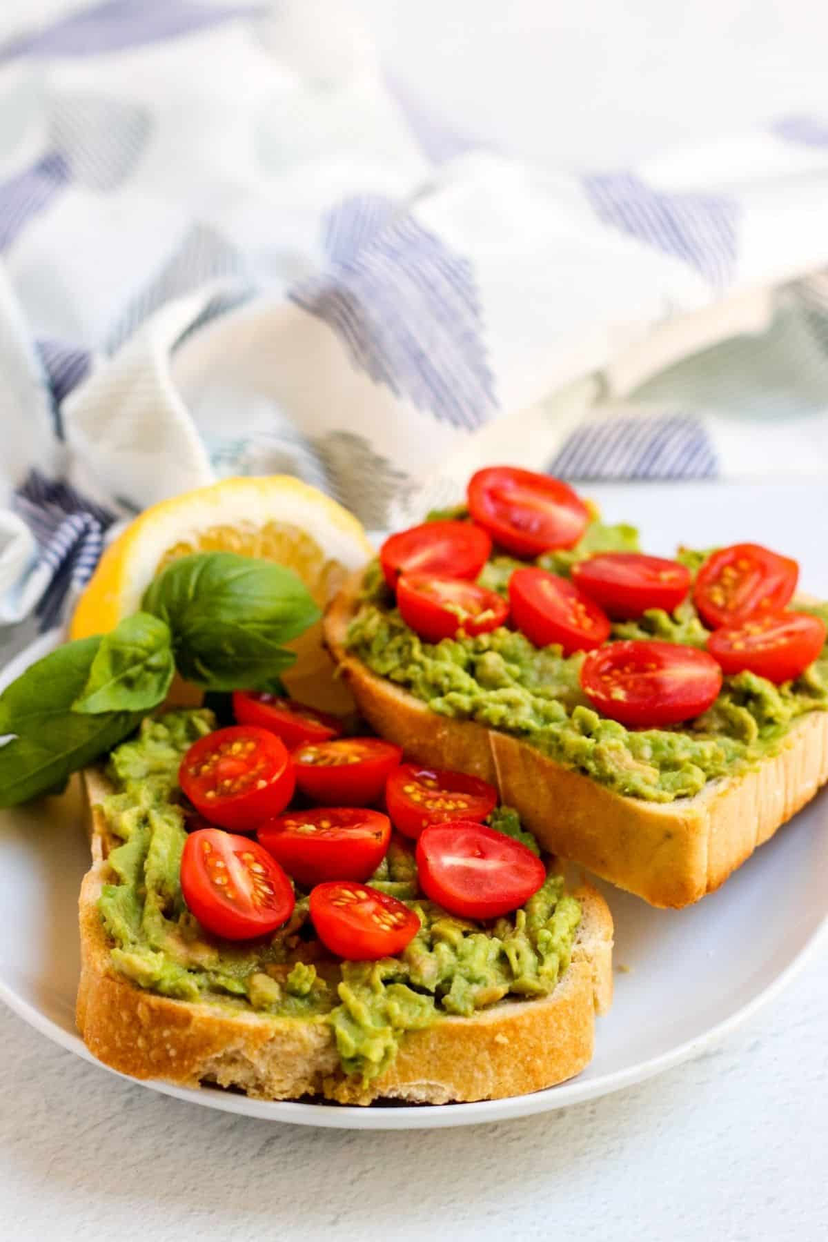 Finished slices of avocado toast on a plate topped with halved cherry tomatoes and garnished with sprig of basil and lemon wedge