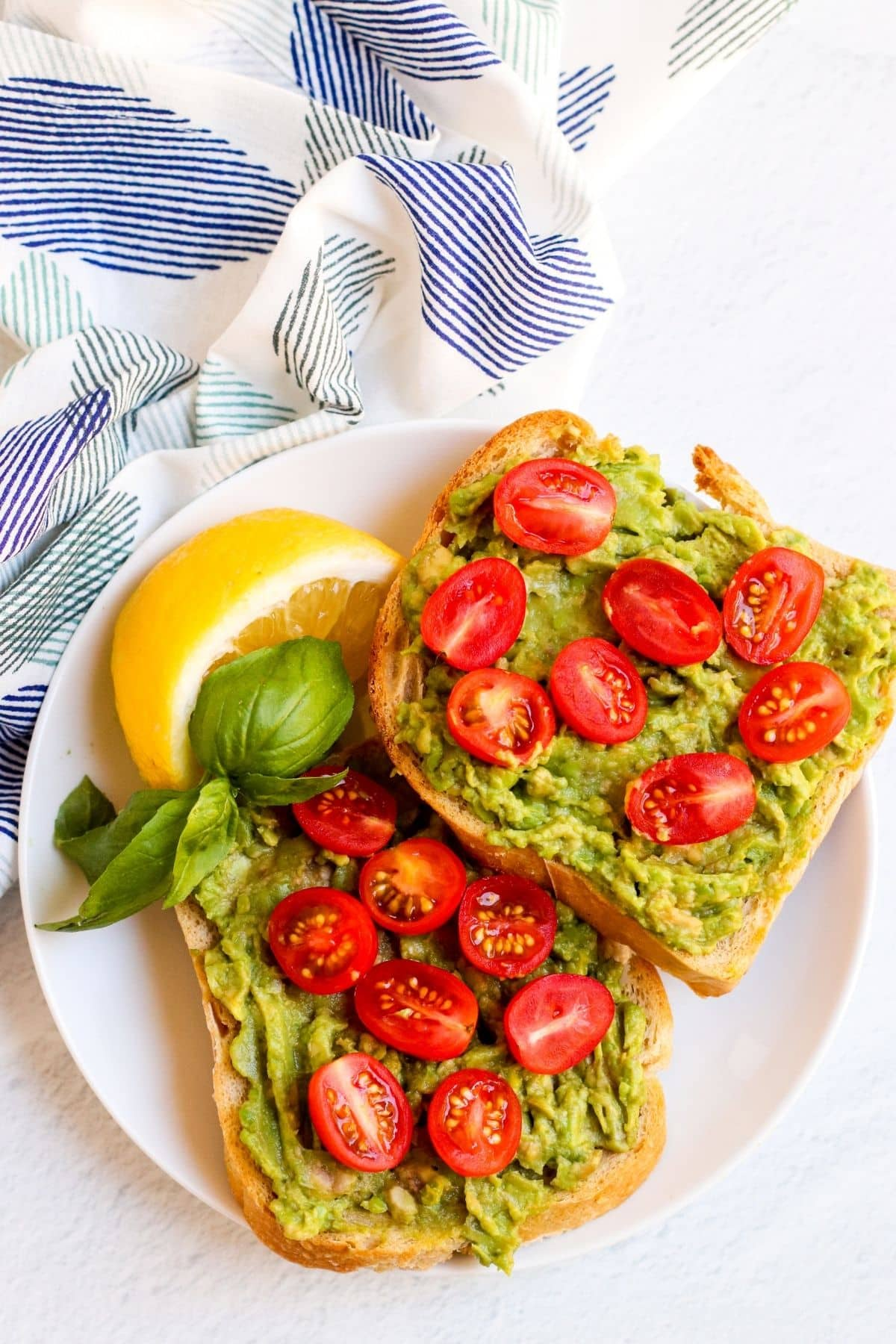 Two slices of avocado toast on a plate topped with halved cherry tomatoes