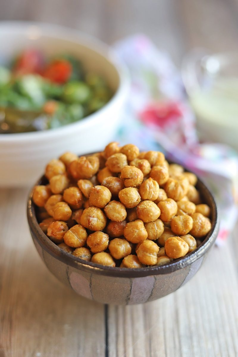 Bowl of chickpeas with salad in the background