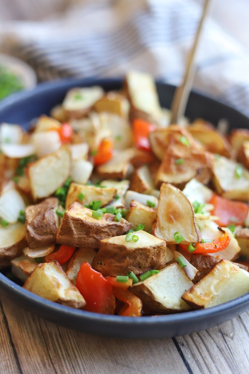 Bowl of potatoes, red bell peppers, and onions garnished with chives