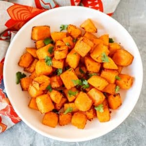 Bowl of butternut squash cubes garnished with fresh cilantro