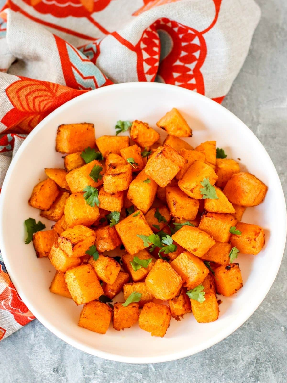 Serving bowl of air fried butternut squash garnished with fresh cilantro