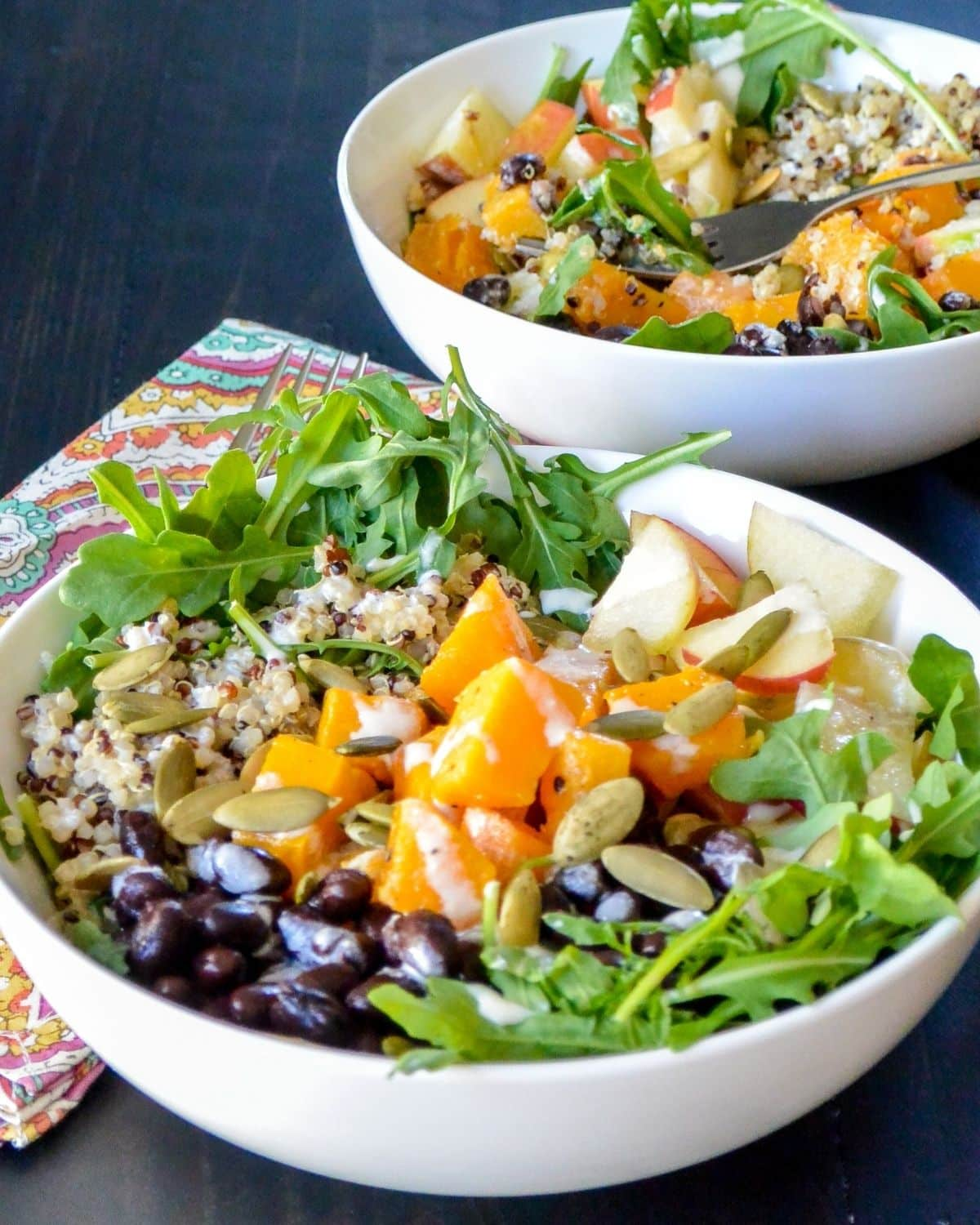 Two quinoa power bowls on a table ready to eat.